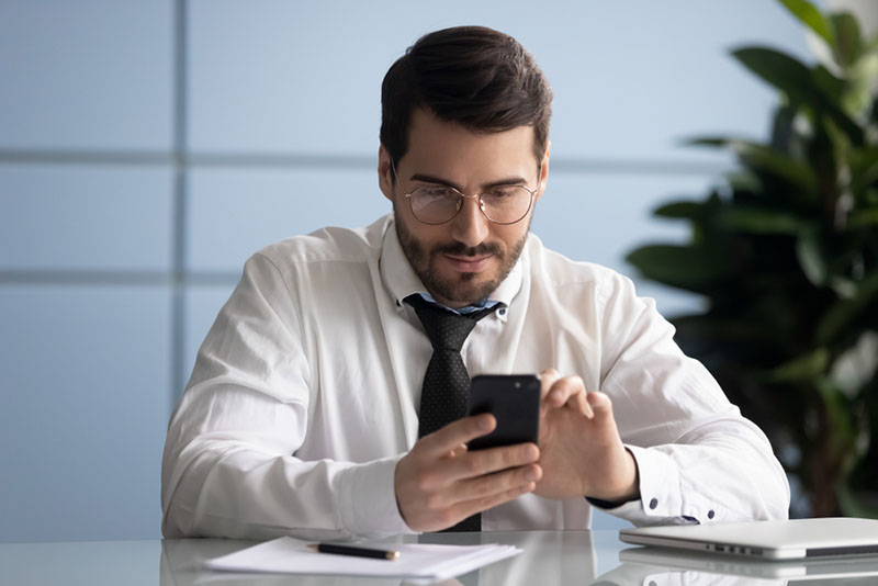 Concentrated millennial male ceo or boss sit at office desk using cellphone browsing fast wireless mobile internet, focused Caucasian businessman surfing web checking mail on modern smartphone